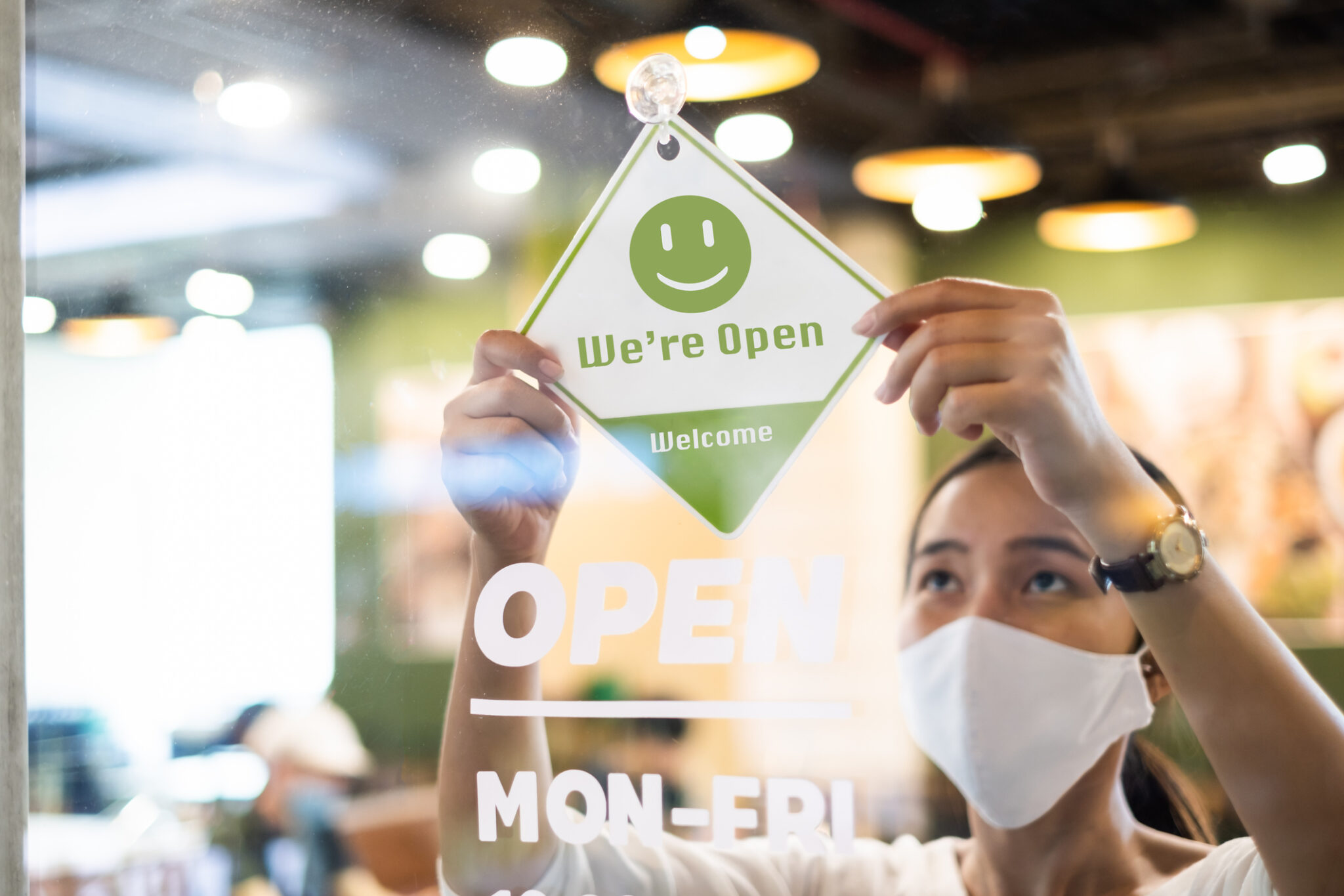 Business woman wearing protective face mask hanging open sign at her restaurant